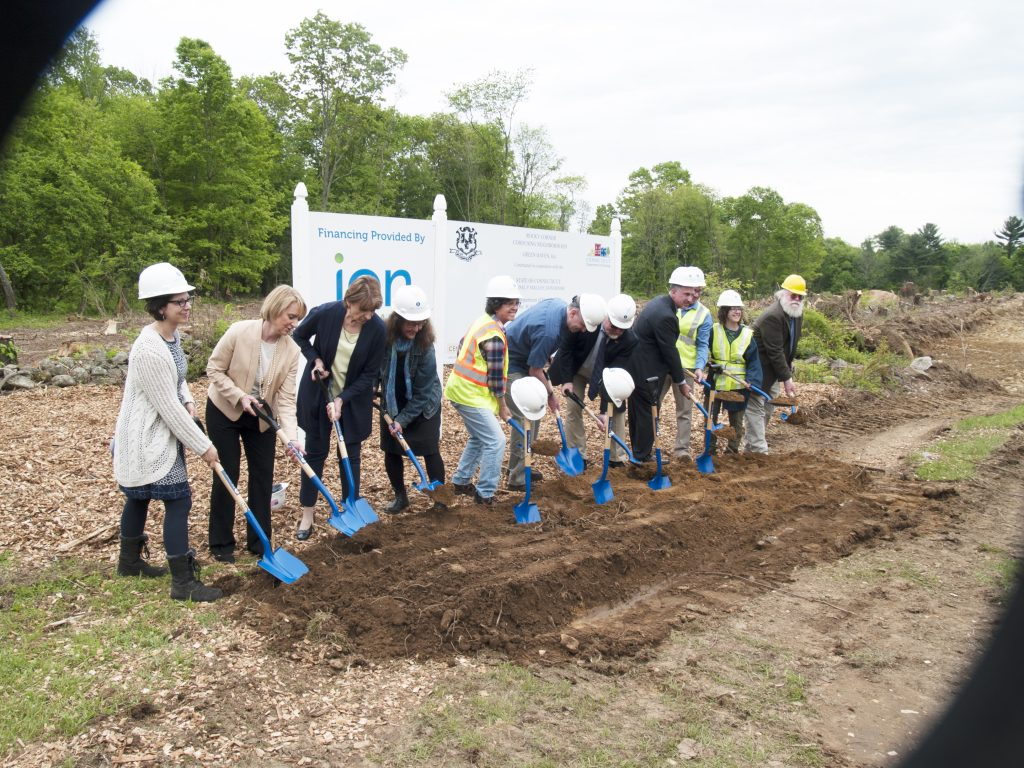 Eleven people standing in a row in front of project funding signs, pretending to shovel dirt, pretty much like every other groundbreaking photo.