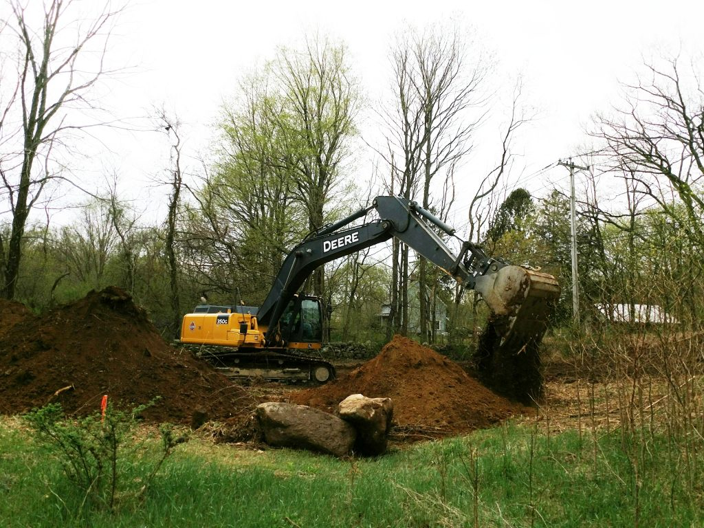 Power shovel dumping dirt on a pile.